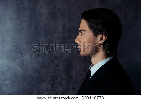 Side-view photo of harsh young man in formalwear.