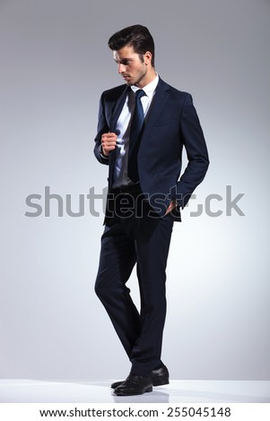 Side view picture of a elegant business man holding one hand in his pocket while pulling his jacket. - stock photo