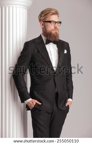 Side view picture of a elegant young man wearing a tuxedo. He is posing near a white column holding both hands in his pockets. - stock photo