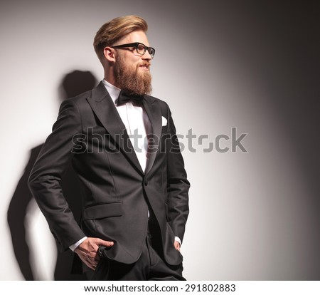 Side view picture of a happy young business man holding both hands in pockets while looking away from the camera.