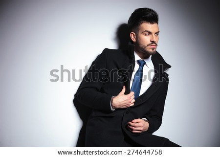 Side view picture of a young business man fixing his coat while looking away from the camera. - stock photo