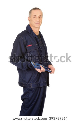 Side view plumber holding a wrench - stock photo