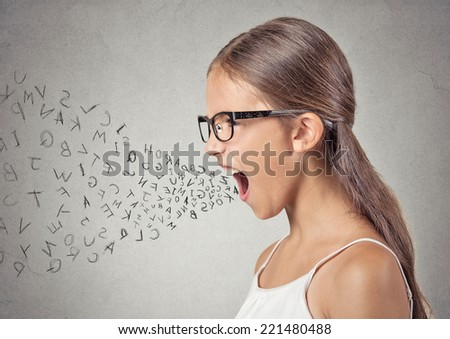 Side view portrait angry child screaming, alphabet letters coming out of her mouth, isolated grey wall background. Negative human face expressions, emotion, reaction. Conflict, confrontation concept - stock photo