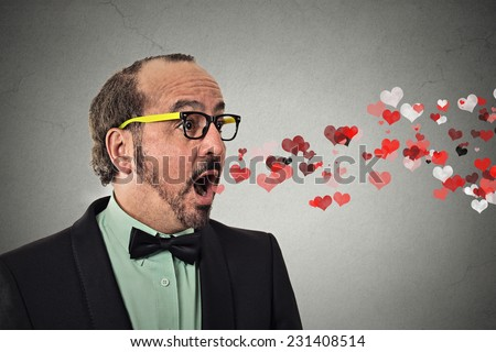 Side view portrait business man sending kisses, red hearts coming flying out of open mouth isolated grey wall background. Positive emotion facial expression feeling life perception. valentines day - stock photo
