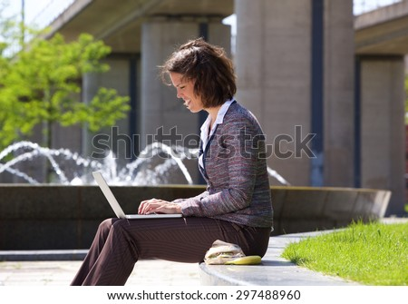 Side view portrait of a business woman working on laptop in the park during her lunch break - stock photo