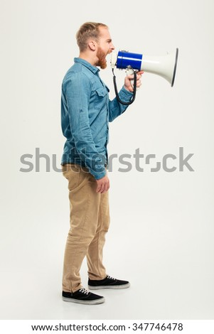 Side view portrait of a casual man screaming in megaphone isolated on a white background - stock photo