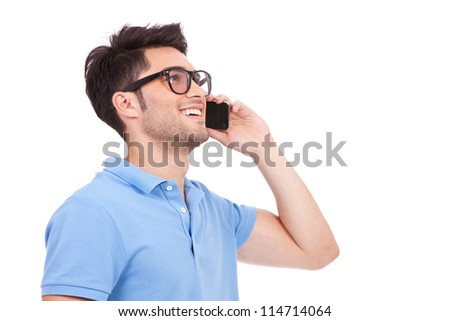 side view portrait of a casual young man speaking on the phone and smiling while looking away, somewhere up. on white background - stock photo