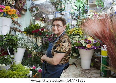 Side view portrait of a confident female florist in shop - stock photo