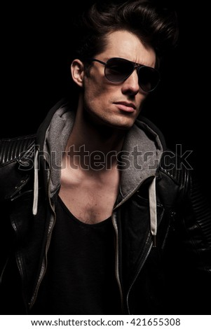 side view portrait of a cool young man in leather jacket and sunglasses looking away from the camera in studio - stock photo