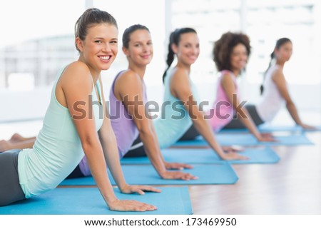 Side view portrait of a fit class doing the cobra pose in a bright fitness studio - stock photo