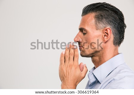 Side view portrait of a handsome man praying over gray background - stock photo
