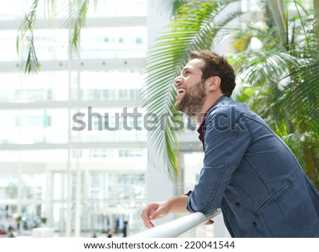 Side view portrait of a handsome young man leaning inside bright building - stock photo