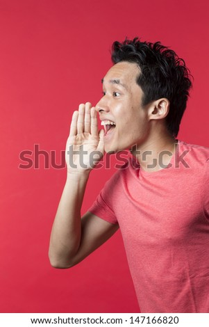 Side view Portrait of a happy Chinese/Asian man shouting. Red background. - stock photo