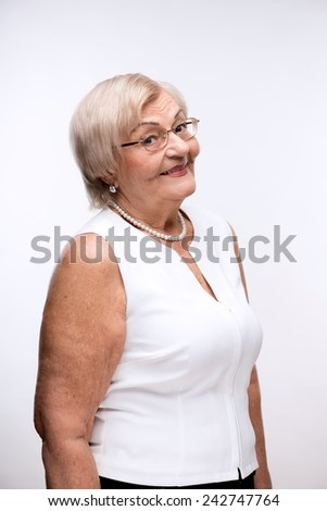 Side view portrait of a happy elegant retired woman posing in white blouse and glasses while standing against white background - stock photo