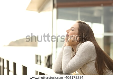 Side view portrait of a happy relaxed woman breathing fresh air outdoor in an hotel or apartment in the beach - stock photo