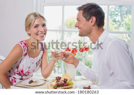 Side view portrait of a happy young couple toasting wine glasses over food at home
