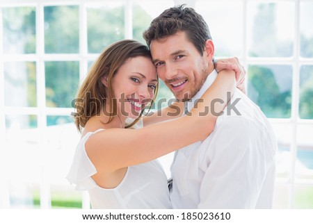 Side view portrait of a loving young couple standing at home - stock photo