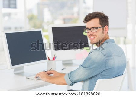 Side view portrait of a male artist using computer in the office - stock photo