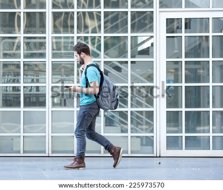 Side view portrait of a male student walking on campus with bag and mobile phone - stock photo