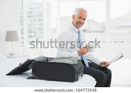 Side view portrait of a mature businessman with coffee cup reading newspaper by luggage at a hotel room - stock photo