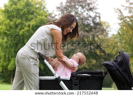 Side view portrait of a mother putting baby into pram - stock photo