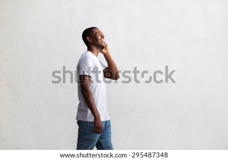 Side view portrait of a smiling african american guy walking and talking on mobile phone - stock photo