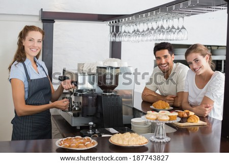 Side view portrait of a smiling couple with female cafe owner at the coffee shop