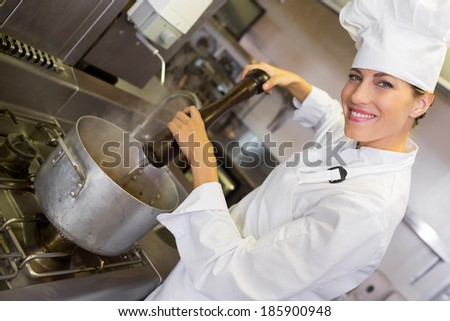 Side view portrait of a smiling female cook preparing food in the kitchen