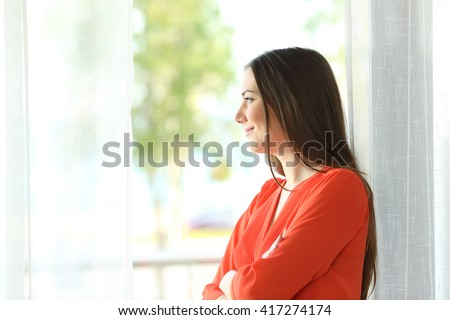 Side view portrait of a thoughtful attractive female looking the green background outside through a window of an hotel room or home - stock photo