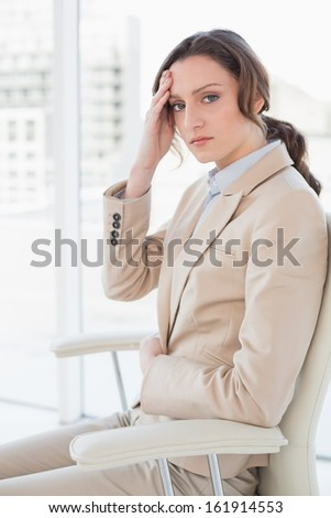 Side view portrait of a young businesswoman suffering from headache in a bright office
