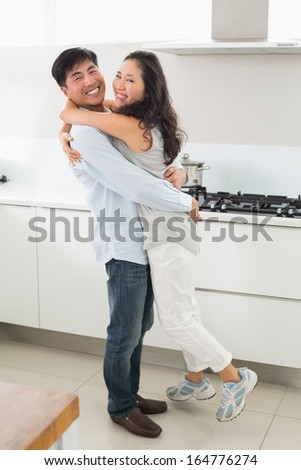 Side view portrait of a young man embracing woman in the kitchen at home - stock photo