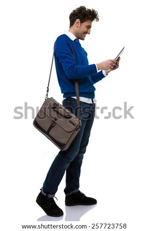 Side view portrait of a young man using tablet computer over white background - stock photo
