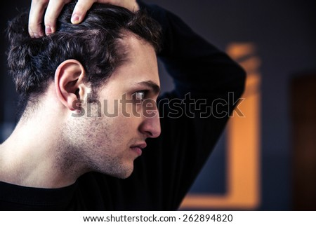 Side view portrait of a young man with curly hair - stock photo