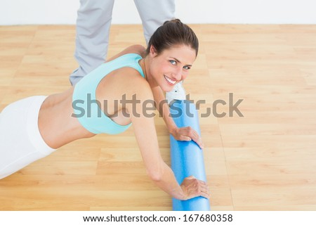 Side view portrait of a young woman do push ups in the gym at hospital - stock photo