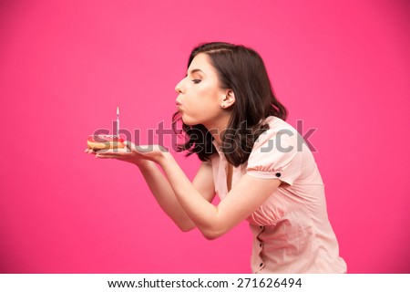 Side view portrait of a young woman holding donut and blowing on candle over pink background - stock photo