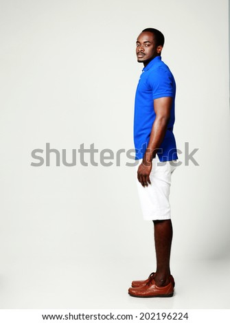 Side view portrait of african man standing on gray background - stock photo