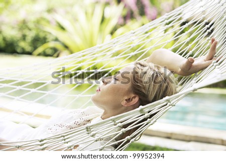 Side view portrait of an attractive blonde woman laying down on a hammock in a garden, sleeping. - stock photo