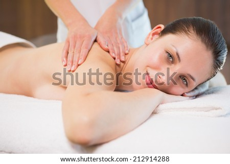 Side view portrait of an attractive young woman receiving back massage at spa center