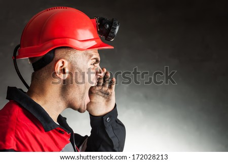 Side view portrait of angry coal miner shouting against a dark background