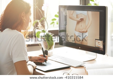 Side view portrait of attractive woman retoucher working on the computer, hand drawing on graphic tablet. Young Caucasian female photographer with red hair in white T-shirt editing photos at home  - stock photo