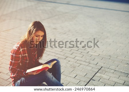 Side view portrait of attractive young girl enjoying a good book sitting at sunny evening outdoors - stock photo