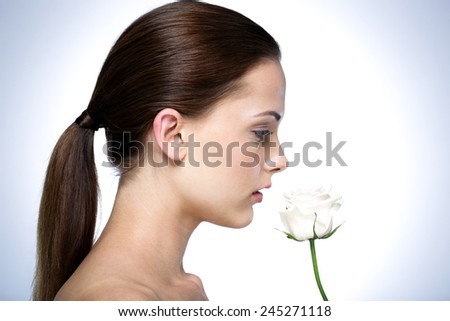 Side view portrait of attractive young woman with flower - stock photo