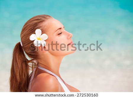 Side view portrait of beautiful calm female with frangipani flower in hair meditating on the beach, enjoying day spa, summer vacation and relaxation