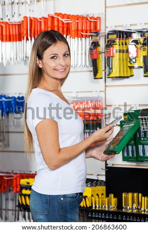 Side view portrait of beautiful customer scanning product's barcode through cellphone in hardware store - stock photo