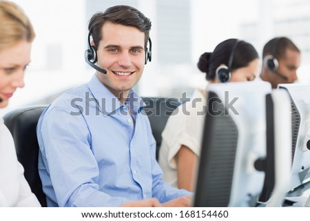 Side view portrait of business colleagues with headsets using computers at office