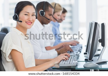 Side view portrait of business colleagues with headsets using computers at office desk