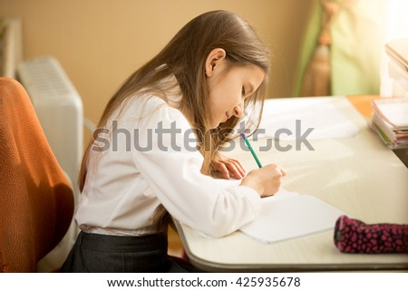 Side view portrait of concentrated schoolgirl writing at exercise book - stock photo