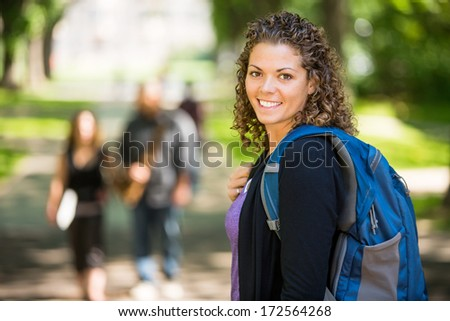 Side view portrait of confident female grad student with backpack standing at campus - stock photo