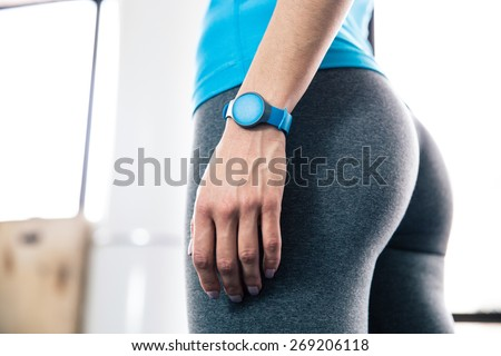 Side view portrait of female body with fitness tracker - stock photo