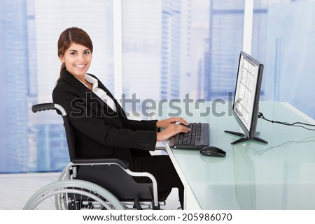 Side view portrait of handicapped businesswoman using computer while sitting on wheelchair in office - stock photo